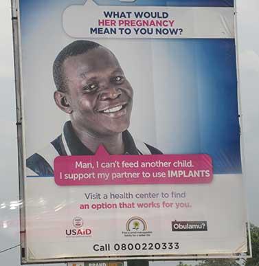 """Manifesto in Uganda che pubblicizza la contraccezione. Nel manifesto è scritto: """"Cosa significherebbe per te ora la sua gravidanza? Ehy amico, non posso sfamare un altro bambino. Io aiuto la mia compagna ad usare gli IMPIANTI"""""""